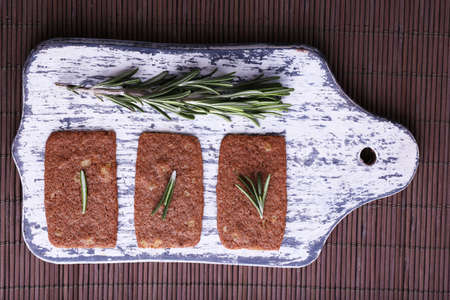 sprigs: Crispbread with sprigs of rosemary on wooden cutting board on bamboo mat background Stock Photo