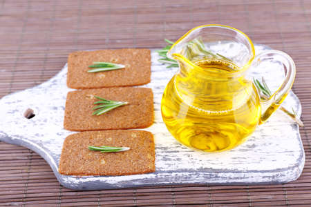 Crispbread with sprigs of rosemary on wooden cutting board with jug of oil on bamboo mat background photo