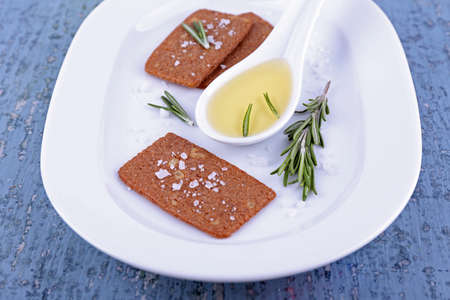Crispbread with salt, spoon of oil and sprigs of rosemary on plate, on color wooden table background photo