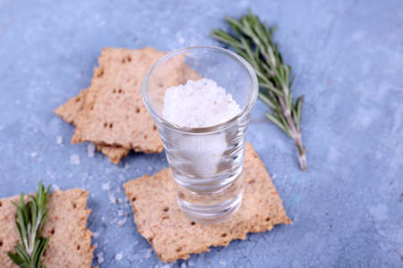 sprigs: Crispbread with salt and sprigs of rosemary on color wooden table background
