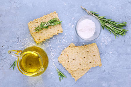 sprigs: Crispbread with salt, jug of oil and sprigs of rosemary on color wooden table background