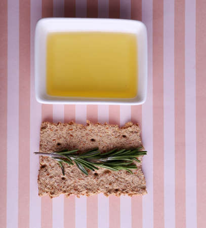 sprigs: Crispbread with oil and sprigs of rosemary on striped background Stock Photo