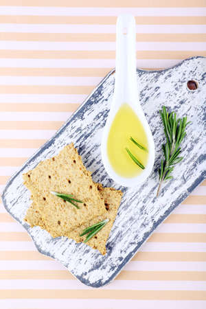 sprigs: Crispbread with spoon of oil and sprigs of rosemary on cutting board, on striped background Stock Photo