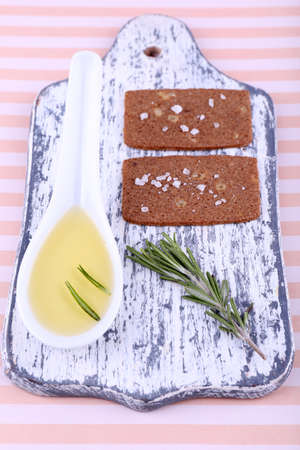Crispbread with salt, spoon of oil and sprigs of rosemary on cutting board, on striped background photo