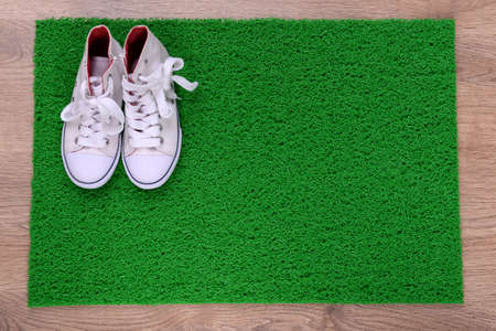 converse: Green carpet on floor and converse close-up
