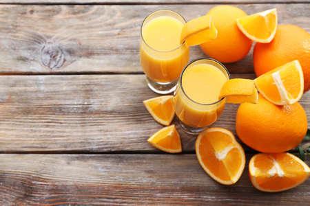 Freshly squeezed orange juice on wooden table photo
