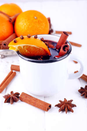 mulled wine spice: Mug of mulled wine with pieces of orange and spice on color wooden background