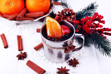 mulled wine spice: Metal mug of mulled wine with orange and spice and branch of Christmas tree on color wooden background