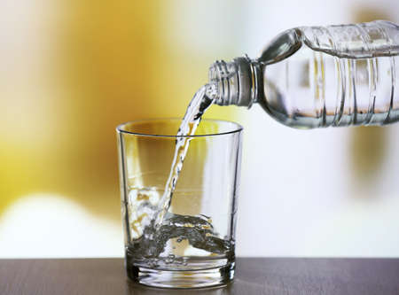 vaso de agua: Verter el agua de la botella de vidrio sobre fondo claro Foto de archivo