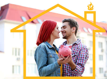 loving couple: Loving couple with piggy bank near apartment house Stock Photo