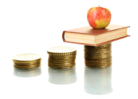 Apple and book standing on stack of coins isolated on white photo
