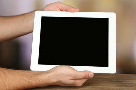Hands holding tablet PC on wooden table and light blurred background photo