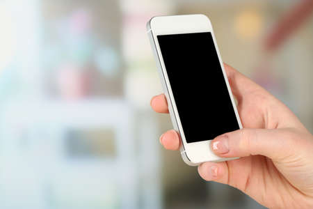 Hand holding smart mobile phone on light blurred background photo