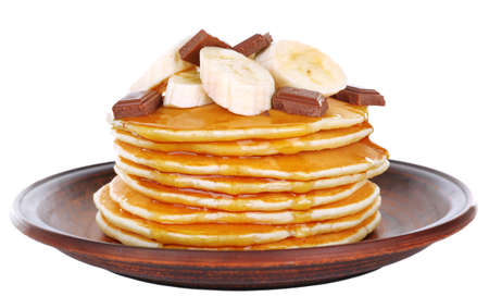 Stack of delicious pancakes with chocolate, honey and slices of banana on plate isolated on white photo