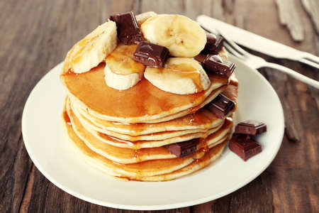 Stack of delicious pancakes with chocolate, honey and slices of banana on plate on wooden table background photo