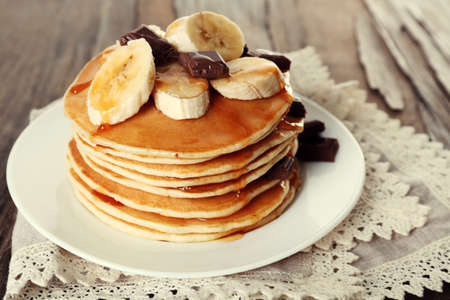 Stack of delicious pancakes with chocolate, honey and slices of banana on plate and napkin on wooden table background photo