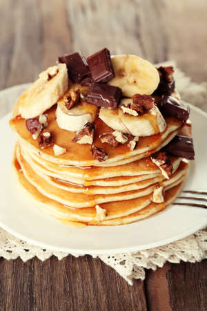 Stack of delicious pancakes with chocolate, honey, nuts and slices of banana on plate and napkin on wooden table background photo