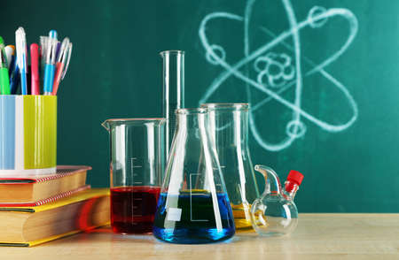 teaching material: Desk in chemistry class with test tubes on green blackboard background Stock Photo