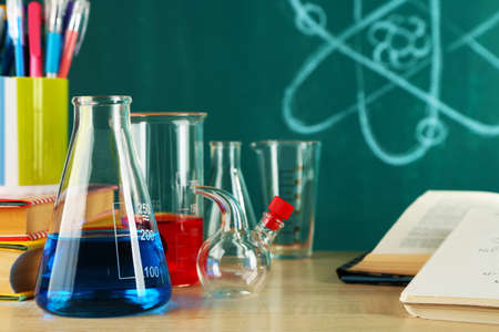 chemistry formula: Desk in chemistry class with test tubes on green blackboard background Stock Photo