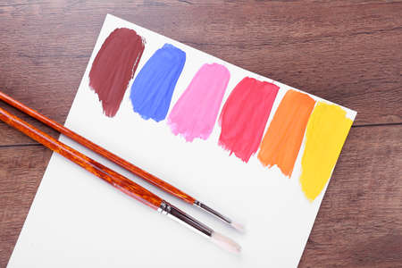 redness: Colorful paint strokes with brush on white sheet of paper on wooden table background Stock Photo