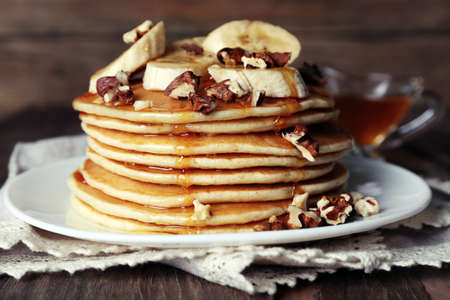 flapjacks: Stack of delicious pancakes with chocolate, honey, nuts and slices of banana on plate and napkin on wooden background Stock Photo
