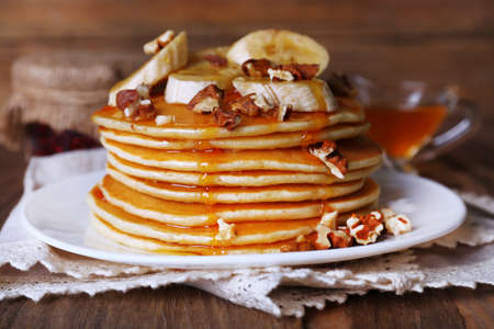 Stack of delicious pancakes with chocolate, honey, nuts and slices of banana on plate and napkin on wooden background photo