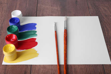paint cans: Colorful paint strokes with brush and paint cans on white sheet of paper on wooden table background Stock Photo