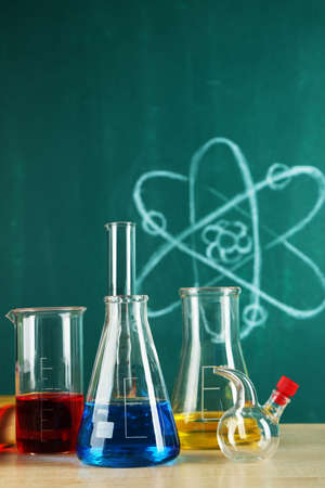 reagents: Desk in chemistry class with test tubes on green blackboard background Stock Photo