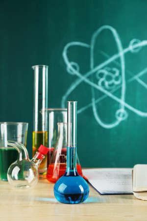 Bureau in chemie klasse met proefbuizen op groene schoolbord achtergrond