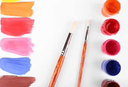 paint cans: Colorful paint strokes with brush and paint cans on white sheet of paper background