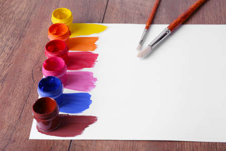 Colorful paint strokes with brush and paint cans on white sheet of paper on wooden table background photo