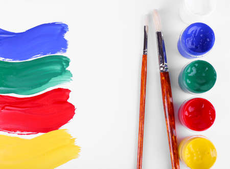 redness: Colorful paint strokes with brush and paint cans on white sheet of paper background