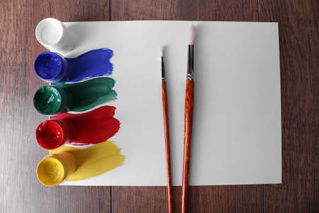 redness: Colorful paint strokes with brush and paint cans on white sheet of paper on wooden table background Stock Photo