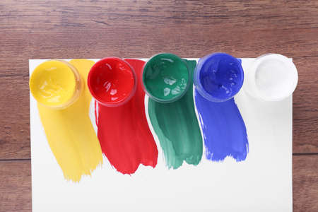 paint cans: Colorful paint strokes with paint cans on white sheet of paper on wooden table background
