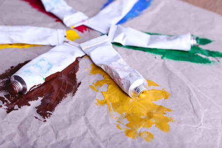 Colorful paint strokes with paint tubes on sheet of paper background photo