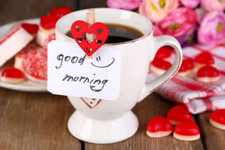 red morning: Cup of tea with card that says good morning on table close-up