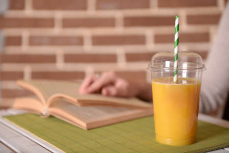 Female hand at table with fast food closed cup of orange juice on brick wall background photo