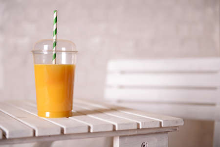 tubes: Orange juice in fast food closed cup with tube on wooden table and light wall background
