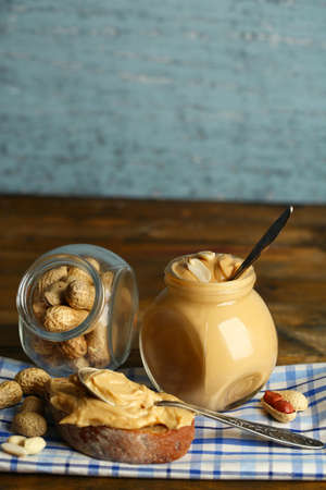 Tasty sandwich and jar with fresh peanut butter on wooden background photo