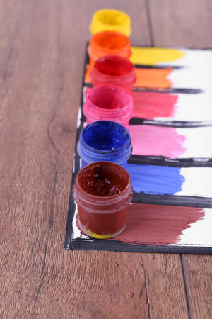 Colorful paint strokes with paint cans on white sheet of paper on wooden table background photo