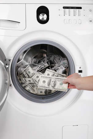 Female putting money into washing machine, closeup photo