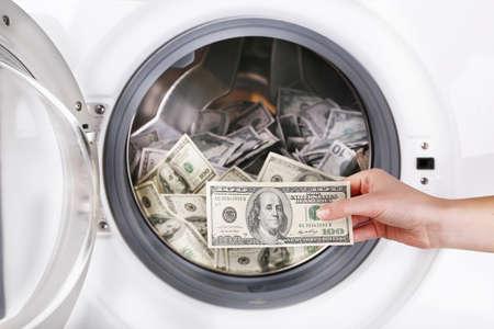 pecuniary: Female putting money into washing machine, closeup