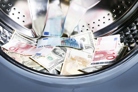 money laundering: Money in washing machine, closeup view