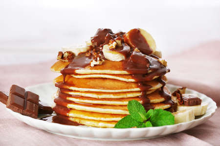 Stack of pancakes with mint, walnuts, chocolate and slices of banana on table with fabric on wooden planks background photo