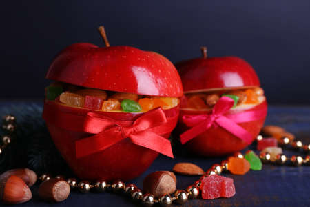 Red apples stuffed with dried fruits on color wooden table and dark background photo