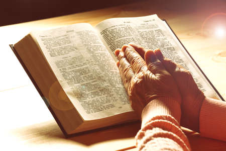 credo: Hands of old woman with Bible on table, close-up
