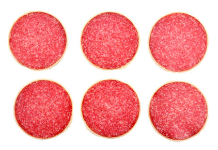 abreast: Slices of salami isolated on white background