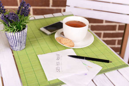 Cup of tea with pen and business notes on napkin on table with green bamboo mat and brick wall background photo