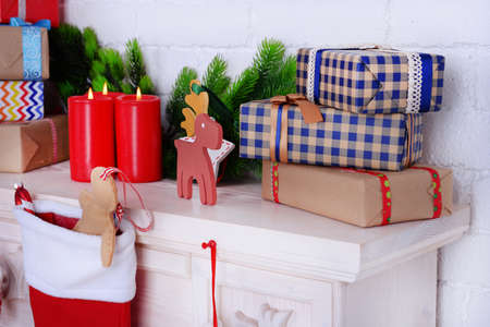 mantelpiece: Mantelpiece with gifts and Christmas decoration on brick wall background Stock Photo