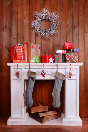 Fireplace with gifts and Christmas decoration on wooden wall background Stock Photo